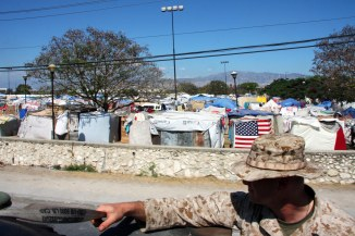 Tent cities house thousands of Haitians left homeless in Port-au-Prince, Haiti as Marines from Combat Logistics Battalion 24, 24th Marine Expeditionary Unit, travel to the local airport to pick up food and water supplies Feb 2. These supplies are going to the Marines of CLB 24 that are building a convalescent aid facility for Haitians returning from USNS Comfort to their homes in Haiti. (U.S. Marine Corps photo by Sgt Andrew J Carlson)