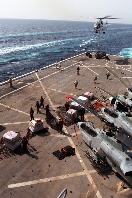 While underway the Marines of the 24th Marine Expeditionary Unit and Sailors aboard USS Mesa Verde take on much needed equipment and supplies during a re-supply at sea on July 14. The Marines and Sailors worked together to unload over one hundred palates carrying everything from mechanical equipment and gear to mail, snacks, and morale items from the flight deck to storage units throughout the ship. (US Marine Corps photo by Sgt Andrew J. Carlson)